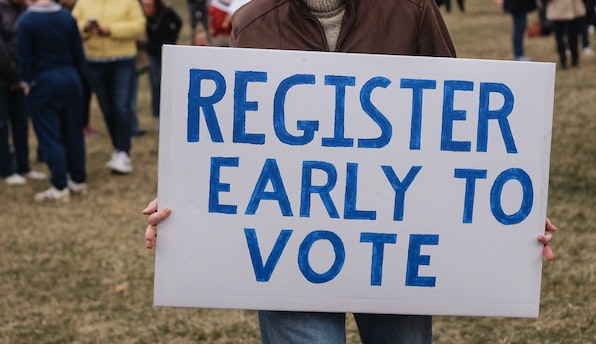 Person holding a register early to vote sign