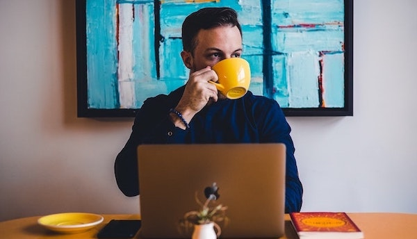Man working remotely in a coffee shop