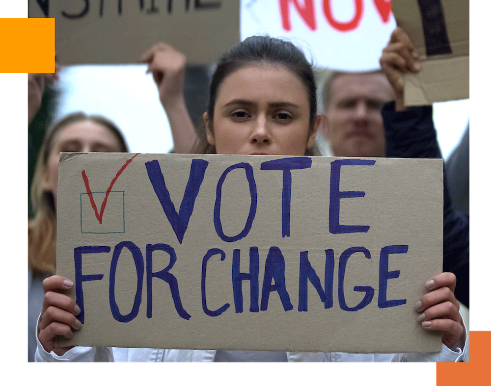 woman holding a sign that reads vote for change